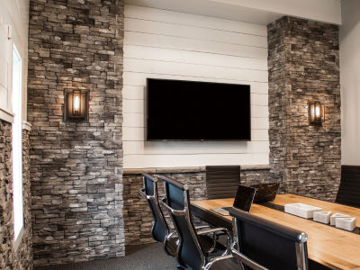 An office interior with stone accent walls, TV and conference room table.